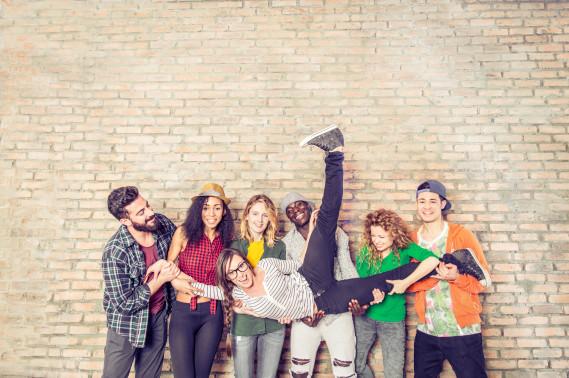 mehrere lachende Jugendliche, die zusammen ein Mädchen auf ihren Händen tragen